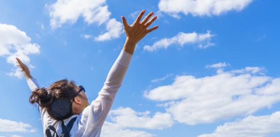 空に向かってバンザイする女性イメージ写真AC